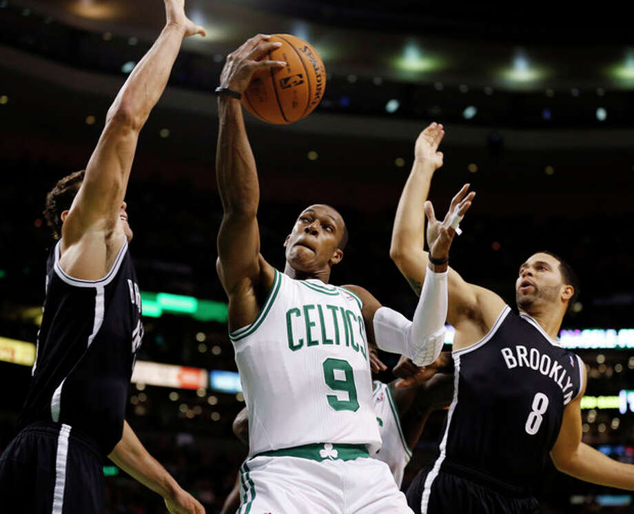 Boston Celtics' Rajon Rondo (9) goes up to shoot between Brooklyn Nets' Kris Humphries, left, and Deron Williams (8) in the first quarter of an NBA basketball game in Boston, Wednesday, Nov. 28, 2012. (AP Photo/Michael Dwyer) / AP
