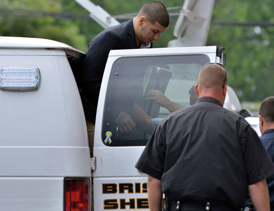 Former New England Patriot football player Aaron Hernandez, is lead from a sheriff's van into a courthouse in Attleboro, Mass., Thursday, Aug. 22, 2013. Hernandez was indicted on first-degree murder and weapons charges in the death of a friend whose bullet-riddled body was found in an industrial park about a mile from the ex-player's home. (AP Photo/Josh Reynolds) / FR25426 AP