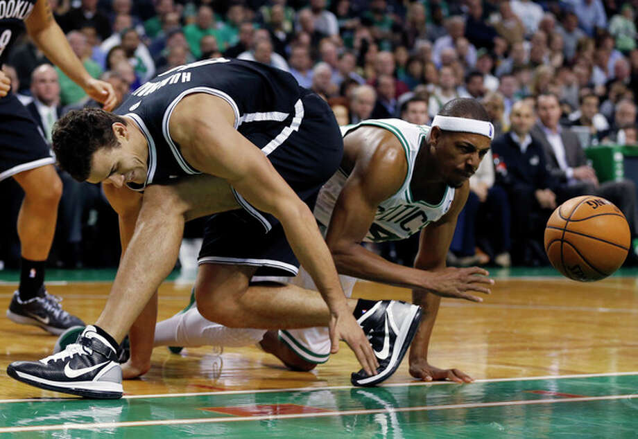 Brooklyn Nets' Kris Humphries, left, and Boston Celtics' Paul Pierce scramble for a loose ball in the second quarter of an NBA basketball game in Boston, Wednesday, Nov. 28, 2012. (AP Photo/Michael Dwyer) / AP