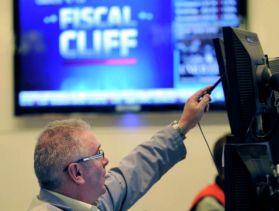 """FILE - In this Nov. 7, 2012, file photo, James Dresch of MND Partners Inc. works on the floor of the New York Stock Exchange in New York. Stocks declined for a third day on Wall Street Wednesday, Nov. 28, 2012, as investors waited for signs of progress on the """"fiscal cliff."""" (AP Photo/Henny Ray Abrams, File) / FR151332"""
