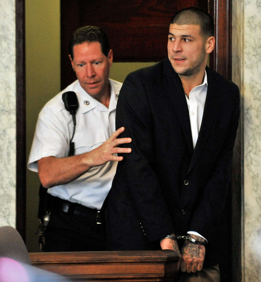 Former New England Patriot football player Aaron Hernandez, is lead into court in Attleboro, Mass., Thursday, Aug. 22, 2013. Hernandez was indicted on first-degree murder and weapons charges in the death of a friend whose bullet-riddled body was found in an industrial park about a mile from the ex-player's home. (AP Photo/Josh Reynolds) / FR25426 AP