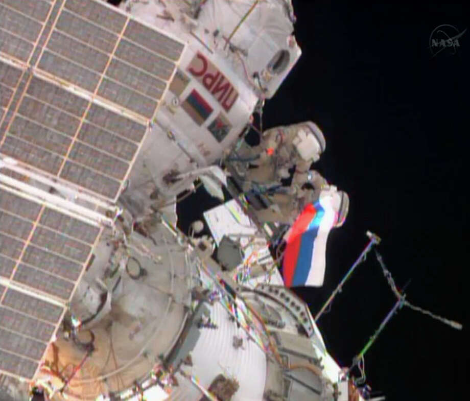 In this image from video made available by NASA, cosmonauts Fyodor Yurchikhin, left, and Aleksandr Misurkin wave a Russian flag near the end of their spacewalk outside the International Space Station on Thursday, Aug. 22, 2013. (AP Photo/NASA) / NASA