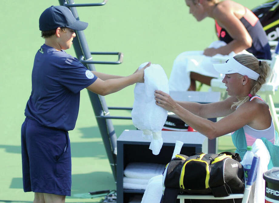 Hour photo/John Nash - David Katz of Weston hands a towel to his favorite player, four-time tournament champion Caroline Wozniacki. Katz and his brother, Nathan, have been ball boys at the New Haven Open for three years.