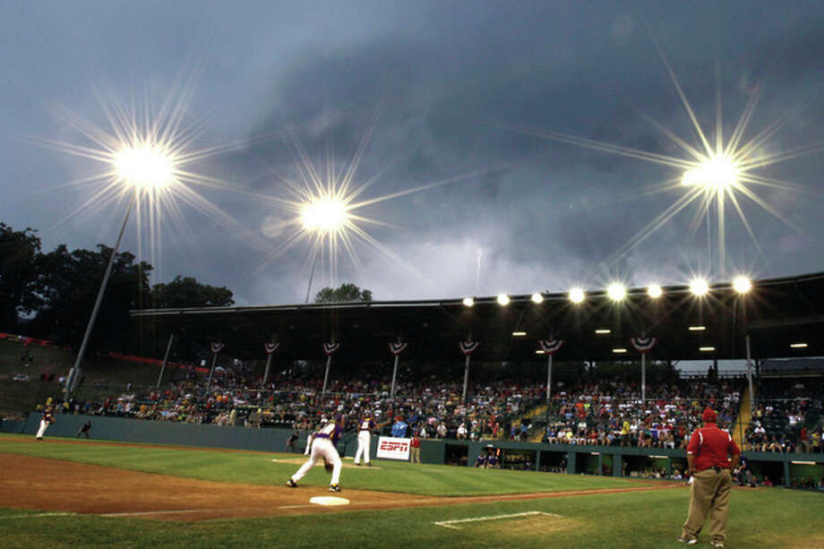 Lightning strikes behind Lamade Stadium during the seventh inning of an elimination baseball game between Aguadulce, Panama, and Tijuana, Mexico, at the Little League World Series tournament on Thursday, Aug. 22, 2013, in South Williamsport, Pa. (AP Photo/Matt Slocum) / AP