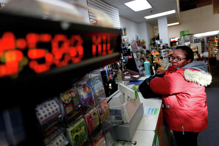 "Pat Powell, 30, of Atlanta, buys a Powerball lottery ticket at a convenience store, Wednesday, Nov. 28, 2012, in Atlanta. ""I think my odds are zero to zero,"" says Powell ""I don't think I'm going to win but I'll just join the hype. If I did win, I'd open up my own business, an internet café in the West Indies and have a learning center here in Georgia. I'll invest and try to be as smart with it as I can with it. I will say for the past 3 days, for whatever reason, I've been thinking about winning this money and what I'd do with it. There's no ritual but it's just been on my mind so it's like, let me just join the hype and just do it."" (AP Photo/David Goldman) / AP"