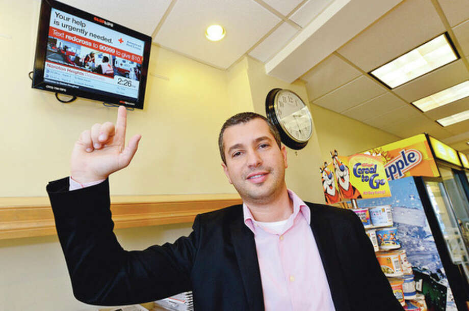Photo by Erik TrautmannManaging founder of StopTips, Kenyon Weiss, at Darien Doughnut. StopTips has monitors that offer tips for Metro-North users and train times and delays. / (C)2012, The Hour Newspapers, all rights reserved