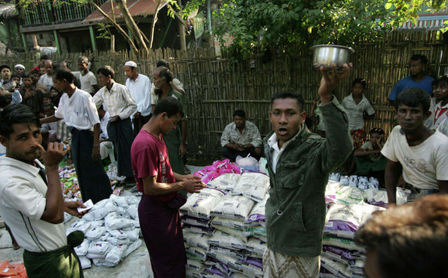 In this photo taken on Nov. 10, 2012, Muslims distribute items to refugees at Sin Thet Maw relief camp in Pauktaw township, Rakhine state, western Myanmar. Myanmar's government has launched a major operation aimed at verifying the citizenship of Muslims in western Rakhine state, the coastal territory that has been torn apart by Buddhist-Muslim violence since June. Questions over whether the region's Muslim Rohingya population qualify for citizenship are at the heart of a crisis that has killed nearly 200 people and displaced 110,000 more. (AP Photo/Khin Maung Win) / AP