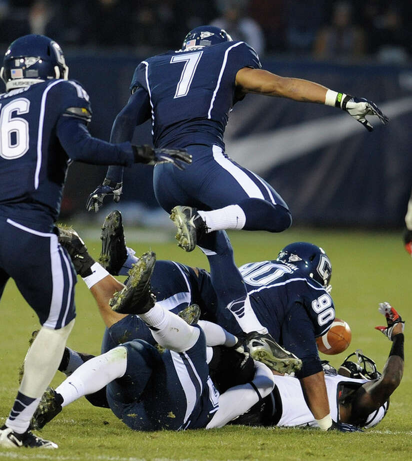 Connecticut defense causes Cincinnati wide receiver Kenbrell Thompkins (7) to fumble the ball during the first half of an NCAA college football game at Rentschler Field in East Hartford, Conn., Saturday, Dec. 1, 2012. (AP Photo/Jessica Hill) / FR125654 AP