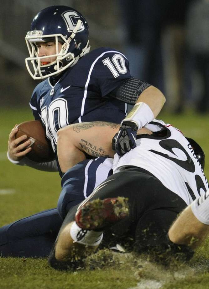 Connecticut quarterback Chandler Whitmer (10), left, is sacked by Cincinnati defensive lineman Dan Giordano (99), right, during the first half of an NCAA college football game at Rentschler Field in East Hartford, Conn., Saturday, Dec. 1, 2012. (AP Photo/Jessica Hill)