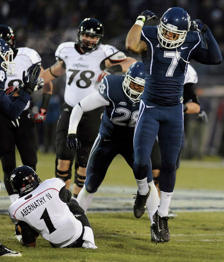 Connecticut cornerback Dwayne Gratz (7), right, reacts after tackling Cincinnati running back Ralph Abernathy (1), left, during the first half of an NCAA college football game at Rentschler Field in East Hartford, Conn., Saturday, Dec. 1, 2012. (AP Photo/Jessica Hill) / FR125654 AP
