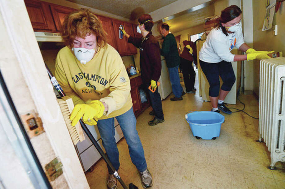 Hour photo / Erik TrautmannVolunteers from St. Thomas the Apostle Church, including Pat Hill, clean the two remaining apartments damaged by Hurricane Sandy, Nos. 707 and 409, at Washington Village Saturday. / (C)2012, The Hour Newspapers, all rights reserved