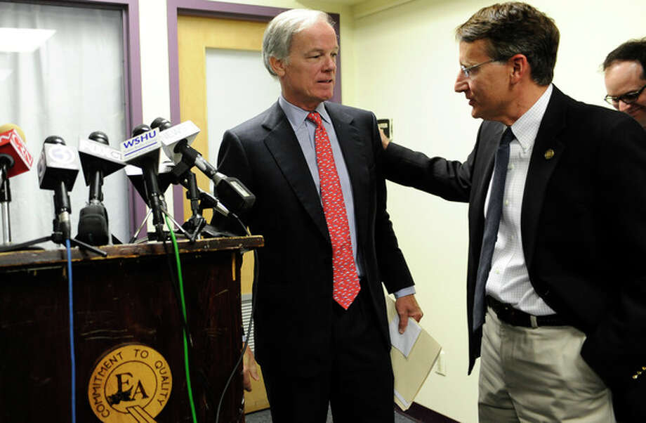 Republican Tom Foley, left, is greeted by Republican state chairman Jerry Labriola after holding a news conference to announce a committee to explore his prospects for the 2014 Connecticut governor's race in Bridgeport, Conn., Tuesday, Sept. 10, 2013. Foley said Tuesday that he is weighing another run for Connecticut governor, attacking the record of the Democrat who defeated him in 2010. (AP Photo/Jessica Hill) / FR125654 AP