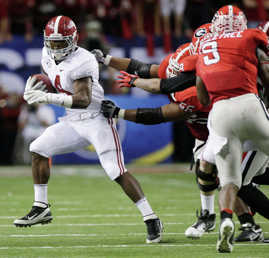 Alabama running back T.J. Yeldon (4) evades several Georgia defenders during the first half of the Southeastern Conference championship NCAA college football†game, Saturday, Dec. 1, 2012, in Atlanta. (AP Photo/Dave Martin) / AP