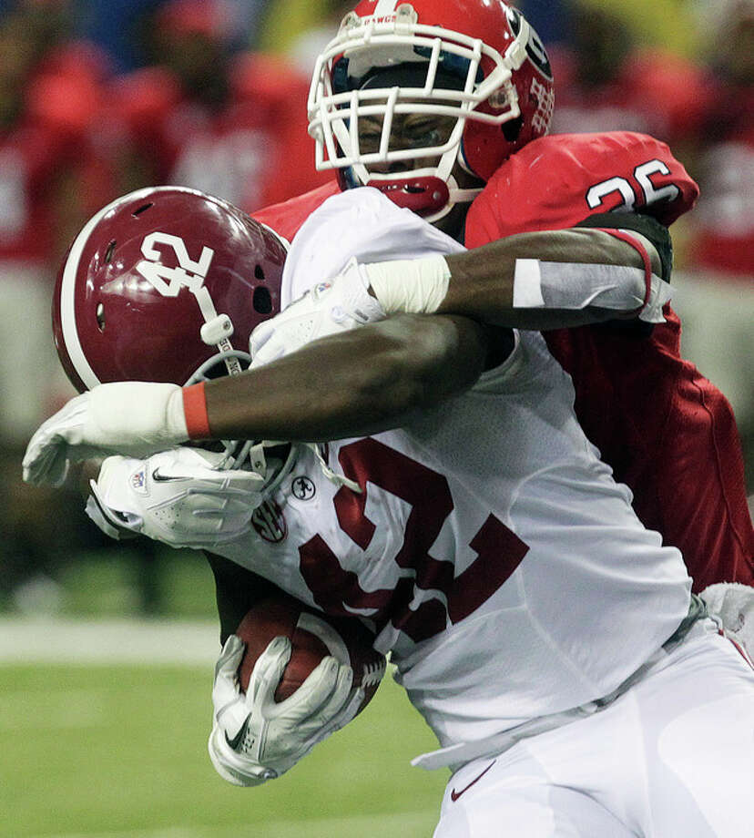 Alabama running back Eddie Lacy (42) is hit by Georgia safety Shawn Williams (36) during the first half of the Southeastern Conference championship NCAA college football†game, Saturday, Dec. 1, 2012, in Atlanta. (AP Photo/Jamie Martin) / FR386386