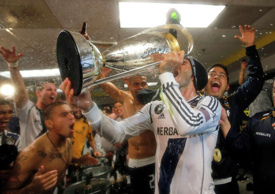 Los Angeles Galaxy's David Beckham, center, of England, drinks champagne from the cup as they celebrate in the dressing room after defeating the Houston Dynamo 3-1 in the MLS Cup championship soccer game, Saturday, Dec. 1, 2012, in Carson, Calif. (AP Photo/Jae C. Hong) / AP