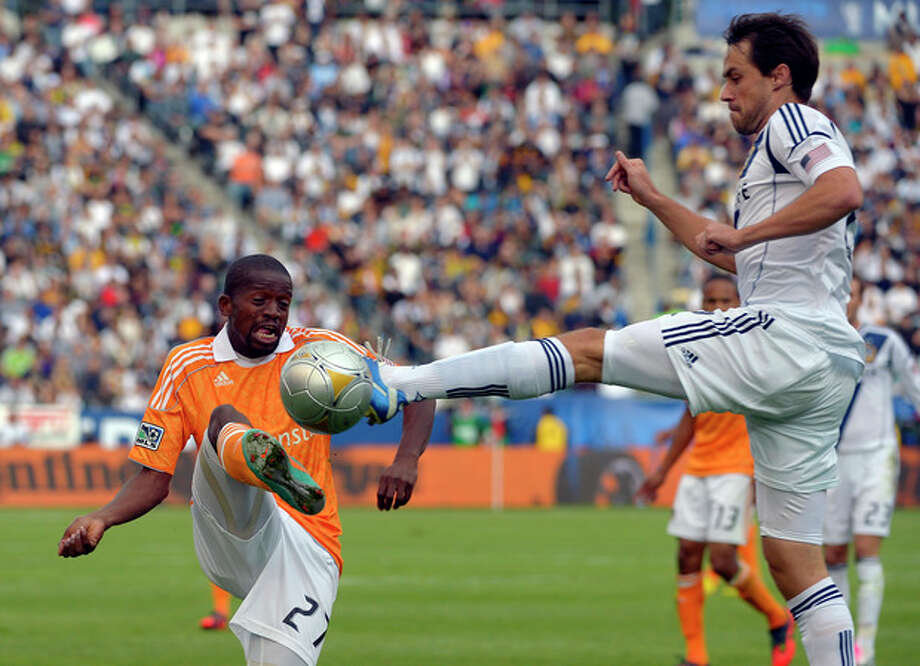 Houston Dynamo midfielder Boniek Garcia, left, and Los Angeles Galaxy defender Todd Dunivant try to kick the ball during the first half of the MLS Cup championship soccer match against the Houston Dynamo in Carson, Calif., Saturday, Dec. 1, 2012. (AP Photo/Jae C. Hong) (AP Photo/Mark J. Terrill) / AP