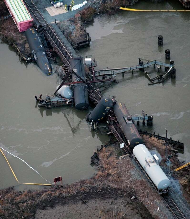 Several cars lay in the water after a freight train derailed in Paulsboro, N.J., Friday, Nov. 30, 2012. People in three southern New Jersey towns were told Friday to stay inside after the freight train derailed and several tanker cars carrying hazardous materials toppled from a bridge and into a creek. (AP Photo/Cliff Owen) / FR170079 AP