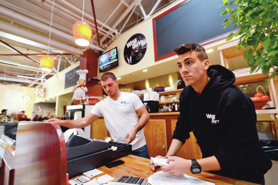 Michael Italiano and Chris Polidoro work the counter at Wise Guys Pizza in SoNo Market. / (C)2012, The Hour Newspapers, all rights reserved