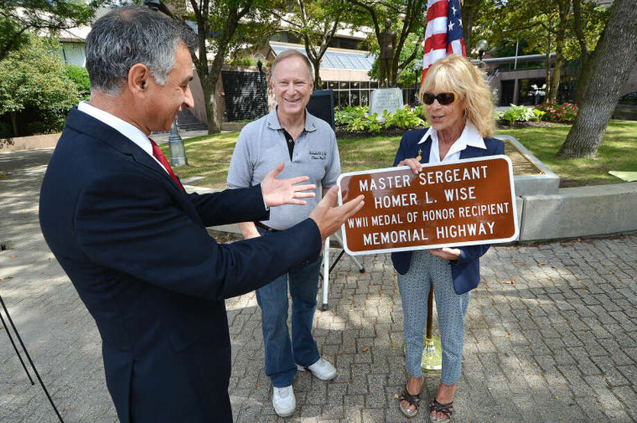 Hour Photo/Alex von Kleydorff. State Senator Carlo Leone presents a plaque to Jeanie Rinalidi, cousin of Homer Wise as cousin Joe Rumore Jr. watches. The plaque is one she can keep, the other one will be placed on the highway dedicated to him