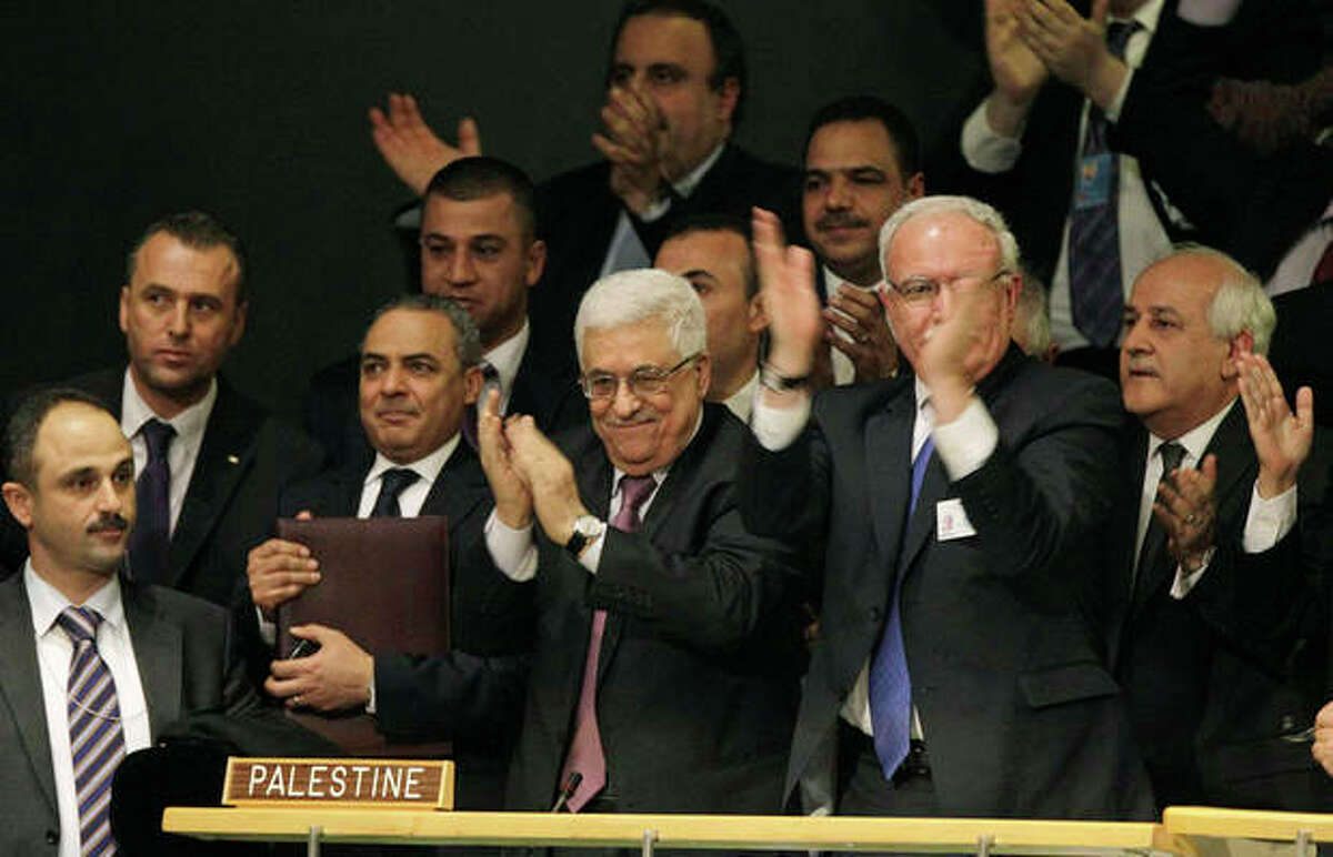 Members of the Palestinian delegation react as they surround Palestinian President Mahmoud Abbas, center, applauding, during a meeting of the United Nations General Assembly after a vote on a resolution on the issue of upgrading the Palestinian Authority's status to non-member observer state passed in the United Nations in New York, Thursday, Nov. 29, 2012. (AP Photo/Kathy Willens)