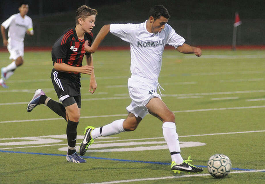 Hour photo/Matthew VinciNorwalk's Rene Jimenez, right, races ahead of New Canaan's Brett Capone during the first half of Tuesday night's season-opening boys soccer game at Testa Field in Norwalk. The Bears, who are the defending state champs, opened the 2013 season with a 2-0 win.
