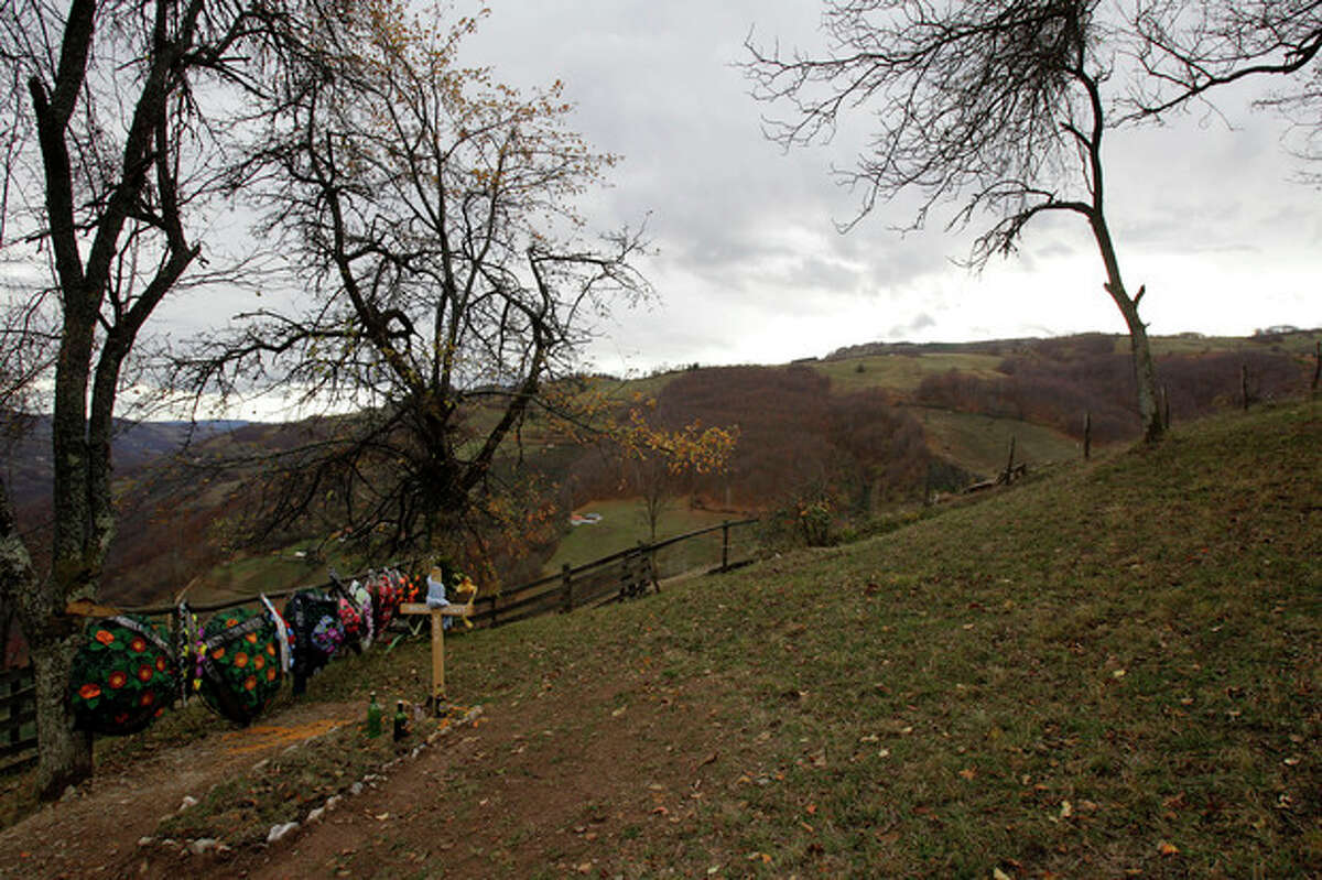 In this Nov. 30, 2012 photo is a grave of a villager in the village of Zarozje, near the Serbian town of Bajina Basta. Get your garlic, wooden crosses and stakes ready: a bloodsucking vampire is on the loose. Or so say villagers in the tiny western Serbian hamlet of Zarozje, nestled between the lush green mountain slopes and spooky thick forests. Rumors that a legendary vampire ghost has returned are spreading panic throughout the town. An official warning telling villagers to put garlic in their pockets and place wooden crosses in each of their rooms, the tools that should keep away the vampires did nothing but fuel the fear. (AP Photo/Darko Vojinovic)