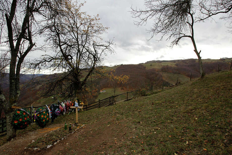 In this Nov. 30, 2012 photo is a grave of a villager in the village of Zarozje, near the Serbian town of Bajina Basta. Get your garlic, wooden crosses and stakes ready: a bloodsucking vampire is on the loose. Or so say villagers in the tiny western Serbian hamlet of Zarozje, nestled between the lush green mountain slopes and spooky thick forests. Rumors that a legendary vampire ghost has returned are spreading panic throughout the town. An official warning telling villagers to put garlic in their pockets and place wooden crosses in each of their rooms, the tools that should keep away the vampires did nothing but fuel the fear. (AP Photo/Darko Vojinovic) / AP