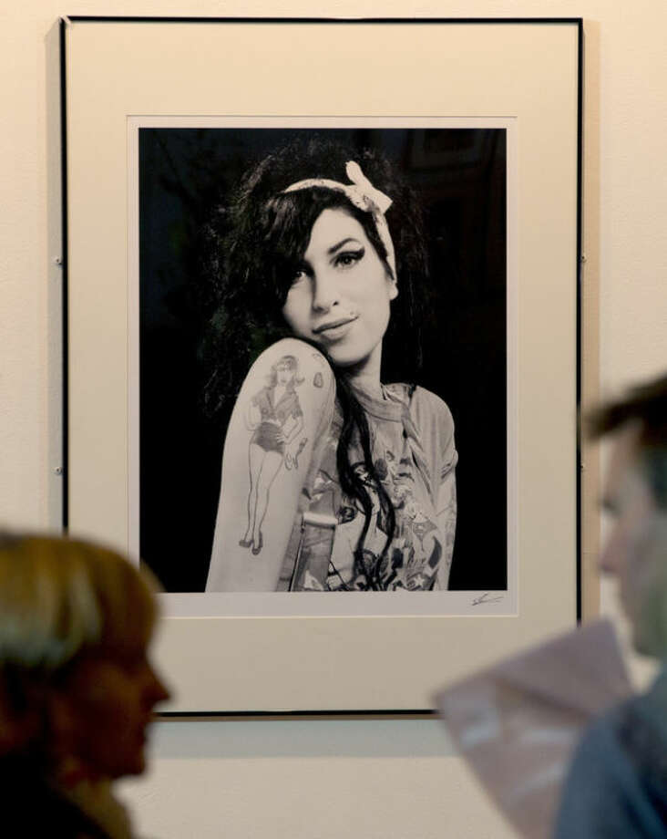 A portrait of the late British singer Amy Winehouse is looked at by members of the media at the Proud gallery in Camden, London, Wednesday, Sept.11,2013. In the month she would have turned 30, Amy Winehouse is being celebrated in Camden the London neighbourhood that was her physical and spiritual home, she died of accidental alcohol poisoning at her house in July 2011, aged 27. The neighbourhood still attracts her fans, and local officials and businesses are holding a series of September events to raise money for the Amy Winehouse Foundation, a youth charity established by the singer's family. (AP Photo/Alastair Grant)