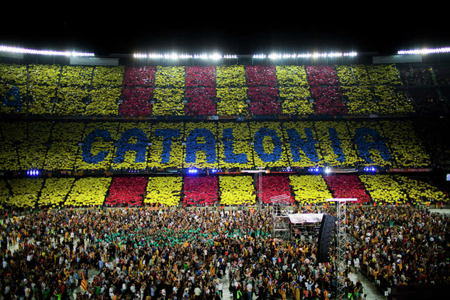 In this photo taken on June. 29, 2013, supporters make a mosaic with the words of Catalonia as they attend to a pro-independence festival in the Nou Camp stadium in Barcelona, Spain. The Spanish region of Catalonia is set to see possibly its largest ever pro-independence rally on Wednesday when organizers are hoping to surpass the around one million people who took to streets of Barcelona last year, many of whom called for a free state. Besides the traditional march in Barcelona held on the regional holiday of Sept. 11, a pro-independence grass roots group has organized a human chain stretching for over 400 kilometers north and south across the economically powerful northeastern region. (AP Photo/Emilio Morenatti) / AP