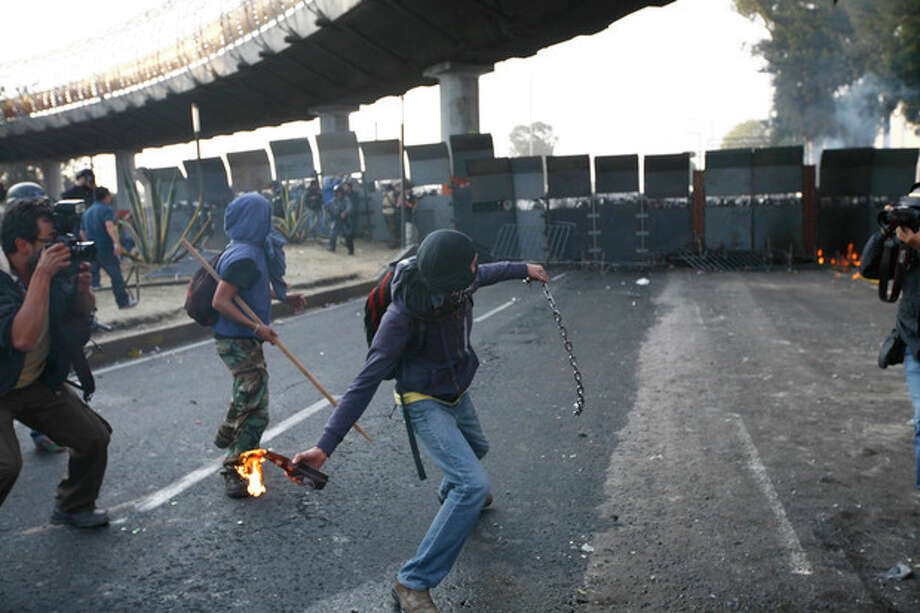 CORRECTS DAY OF THE WEEK TO SATURDAY .- A protestor throws a fire bottle over steel security barriers around the National Congress, where the swearing in of new Mexican President Enrique Pena Nieto will take place in Mexico City, Saturday Dec. 1, 2012. Pena Nieto took power at midnight in a symbolic ceremony and will formally take the oath of office Saturday morning after campaigning as the face of a new PRI _ a party that claims to be repentant and reconstructed after voted out of the presidency in 2000.(AP Photo / Marco Ugarte) / AP
