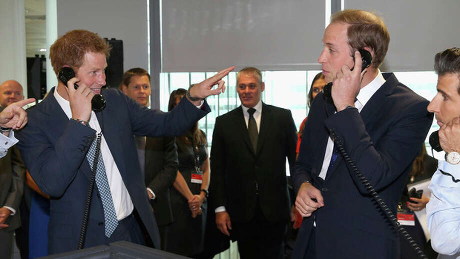 "Britain's Prince William, Duke of Cambridge, right and his brother Prince Harry take part in a trade on the BGC Partners trading floor, during the BGC Charity Day 2013, in Canary Wharf, London, Wednesday, Sept. 11, 2013. Prince William and Prince Harry have turned temporary stock traders, participating in a charity event in memory of victims of the Sept. 11 attacks. Assisted by professional traders, the royals took to the phones for an hour to broker deals, including one valued at 25 billion euros ($33 billion). They also found time to joke around, with Harry accusing his elder brother, father of 2-month-old Prince George, of indulging in ""baby chat"" rather than sealing the deal. (AP Photo/ Chris Jackson, Pool) / Pool Getty"