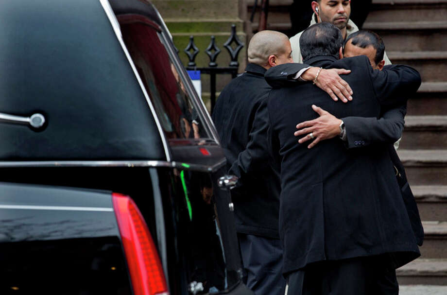 "Mourners hug near a hearse carrying Hector ""Macho"" Camacho's casket near the steps of St. Cecilia's Roman Catholic Church in New York for a funeral, Saturday, Dec. 1, 2012. Doctors pronounced Camacho dead on Saturday, Nov. 24, after he was removed from life support at his family's direction. He never regained consciousness after at least one gunman crept up to his car in a darkened parking lot in Puerto Rico and opened fire. (AP Photo/Craig Ruttle) / FR61802 AP"