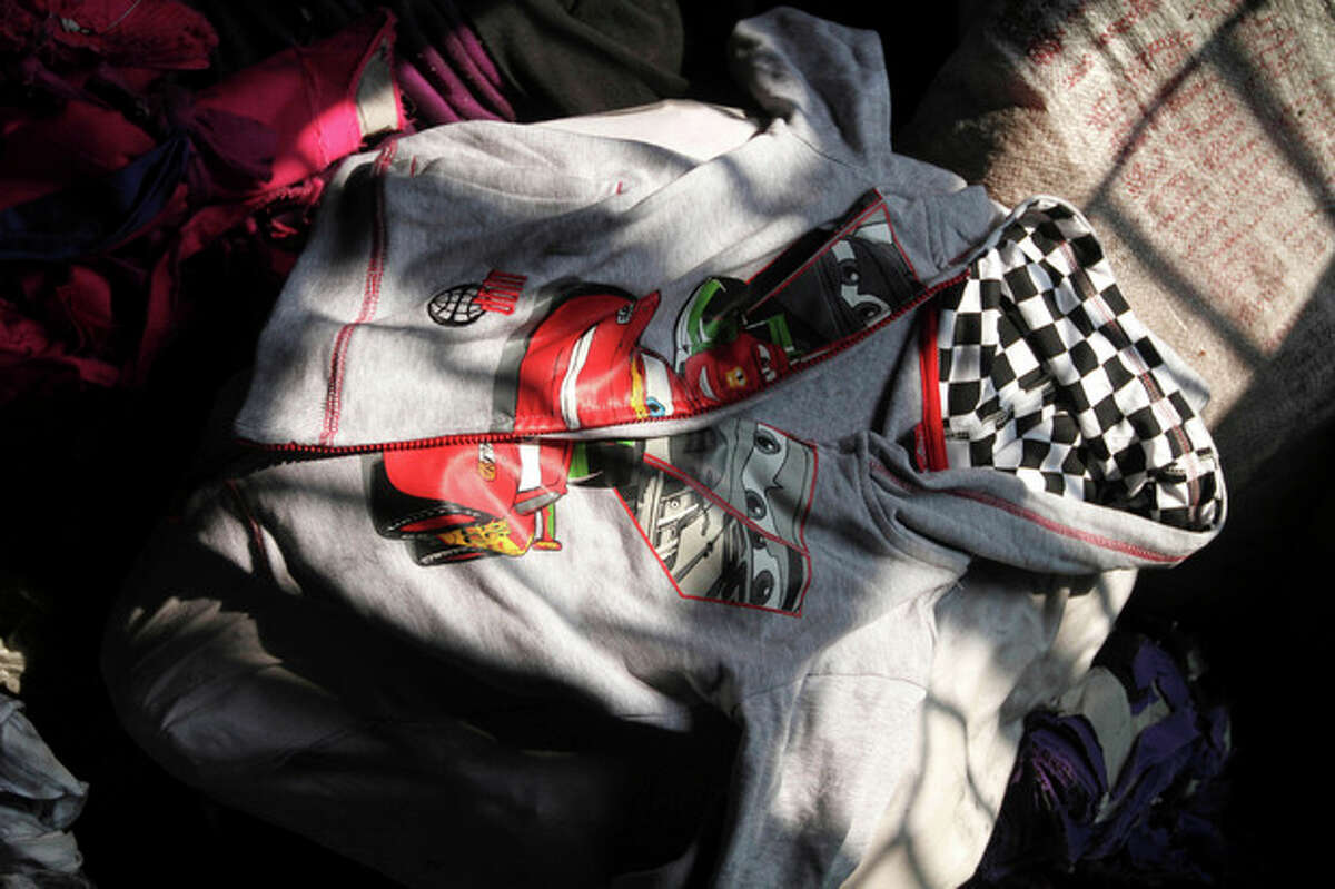 """FILE - This Wednesday, Nov. 28, 2012 file photo shows a Disney brand sweater decorated with characters from the movie """"Cars"""" among the equipment in a burned out garment factory on the outskirts of Dhaha, Bangladesh. A week after a blaze at the factory killed 112 workers, a glaring question remains unanswered: How, exactly, did brands worth fortunes end up in such a place? Retailers like Wal-Mart and Sears, whose merchandise was found in the embers, are loathe to explain. But piecing together their limited answers with records and the insight of industry experts reveals a complex and ever-morphing supply chain, in which Tazreen Fashions Ltd. was but a single, completely interchangeable link. (AP Photo/Ashraful Alam Tito)"""