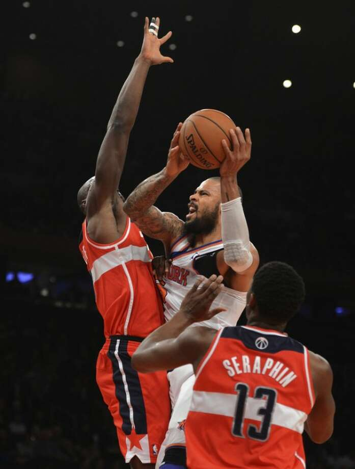 New York Knicks' Tyson Chandler, center, shoots between Washington Wizards' Emeka Okafor, left, and Kevin Seraphin in the first quarter of an NBA basketball game at Madison Square Garden in New York, Friday, Nov. 30, 2012. (AP Photo/Henny Ray Abrams)