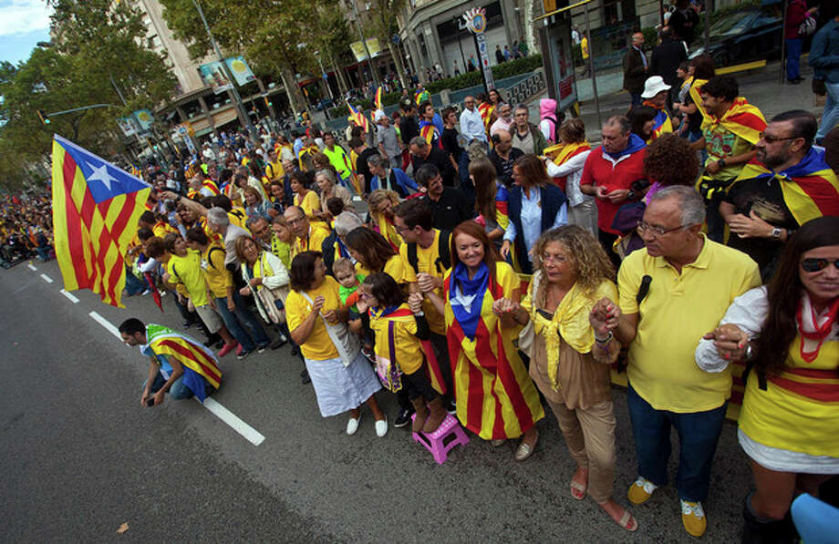 People form a human chain in Barcelona, Spain Wednesday Sept. 11, 2013. Several hundred thousand people demanding an independent Catalonia have joined hands to form a 400-kilometer (250-mile) human chain across the northeastern region of Spain. The demonstration Wednesday aimed to illustrate local support for political efforts to break away from Spain. Organizers estimated about 400,000 people took part in the human chain. Catalonia claims a deep cultural difference based on its language, which is spoken side-by-side with Spanish in the wealthy region. (AP Photo/Joan Manuel Baliellas) / AP