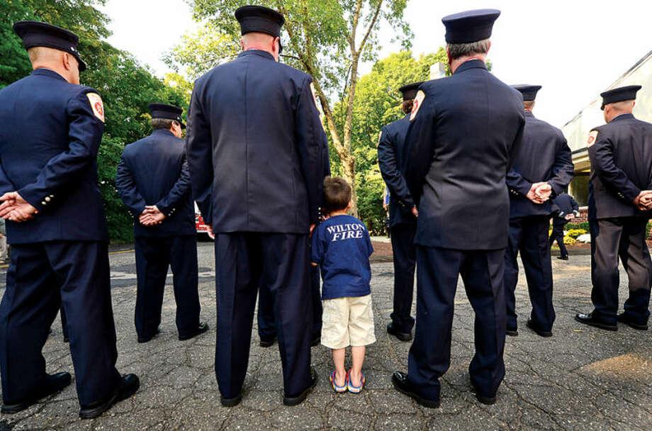 Jackson Elliot accompanies his father Wilton firefighter Brian Elliot during to Wilton 9/11 memorial ceremonies Wednesday at the Wilton Fire Department. Hour photo / Erik Trautmann