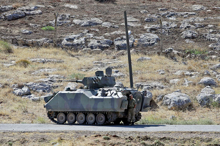 A Turkish soldier stands by a tank as he patrols the border with Syria, near Cilvegozu, Turkey, Wednesday, Sept. 11, 2013. U.S. President Barack Obama conditionally endorsed a Russian offer for international inspectors to seize and destroy deadly chemical weapons in Syria as efforts to avert retaliatory U.S. missile strikes shift from Washington to the United Nations. (AP Photo/Gregorio Borgia) / AP