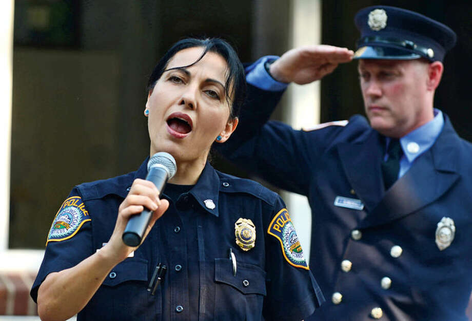 Wilton police officer Anna Tornello sings the National Anthem during the Wilton 9/11 memorial ceremonies Wednesday at the Wilton Fire Department. Hour photo / Erik Trautmann