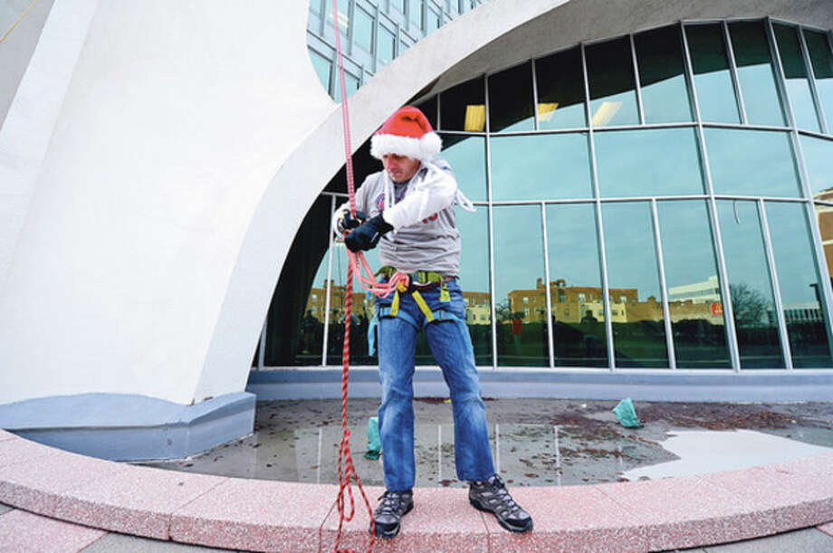 New York Yankees General manager Brian Cashman rappels from Stamford's 1 Landmark Square building Friday in preparation for Sunday nights Christmas tree lighting.Hour photo / Erik Trautmann / (C)2012, The Hour Newspapers, all rights reserved
