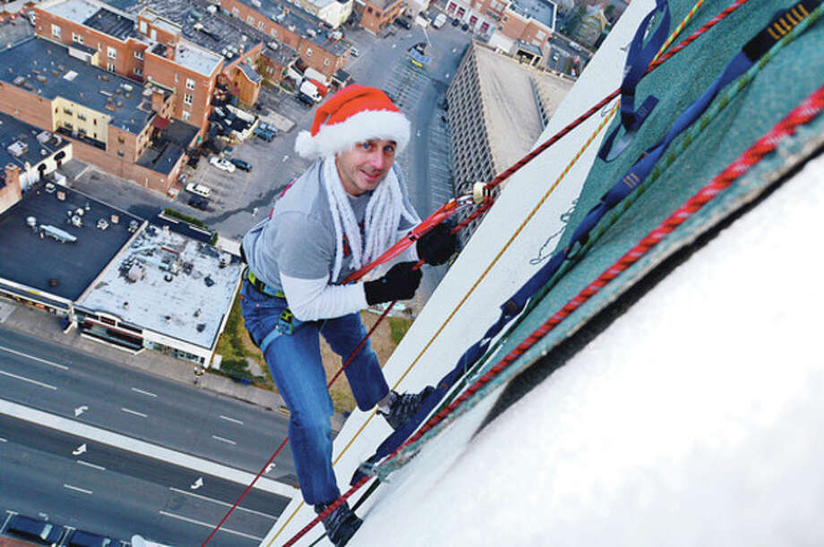 New York Yankees General manager Brian Cashman rappels from Stamford's 1 Landmark Square building Friday in preparationm for Sunday nights Christmas tree lighting.Hour photo / Erik Trautmann / (C)2012, The Hour Newspapers, all rights reserved