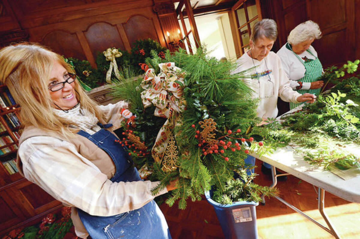 Hour photo / Erik Trautmann Gail Stevens and the Norwalk Garden Club prepare wreaths at Gallaher Mansion on Thursday for its annual Christmas Fair to be held at the Cranbury Chapel on Frank Street on Saturday.
