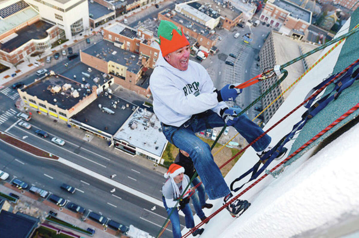 New York Yankees General Manager Brian Cashman and sports great Bobby Valentine rappel from Stamford's 1 Landmark Square building Friday in preparationm for Sunday nights Christmas tree lighting. Hour photo / Erik Trautmann