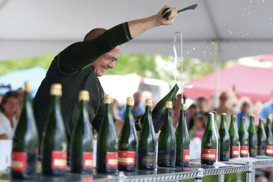 Hour photo / Chris PalermoAncona's Wines & Liquors owner Mitch Ancona sucessfully attempts to open more than 32 champagne bottles in under one minute Sunday afternoon by cutting their tops off with a saber to be in the Guinness Book of World Records. / © 2013 Hour Newspapers All Rights Reserved