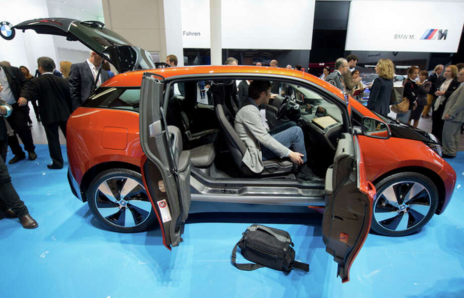Journalists view the i3 electric car by car manufacturer BMW at the Frankfurt Motor Show (IAA) in Frankfurt Main, Germany, Monday, Sept. 9, 2013. The 65th IAA runs Sept 12 through 22, 2013. (AP Photo/dpa, Boris Roessler) / dpa