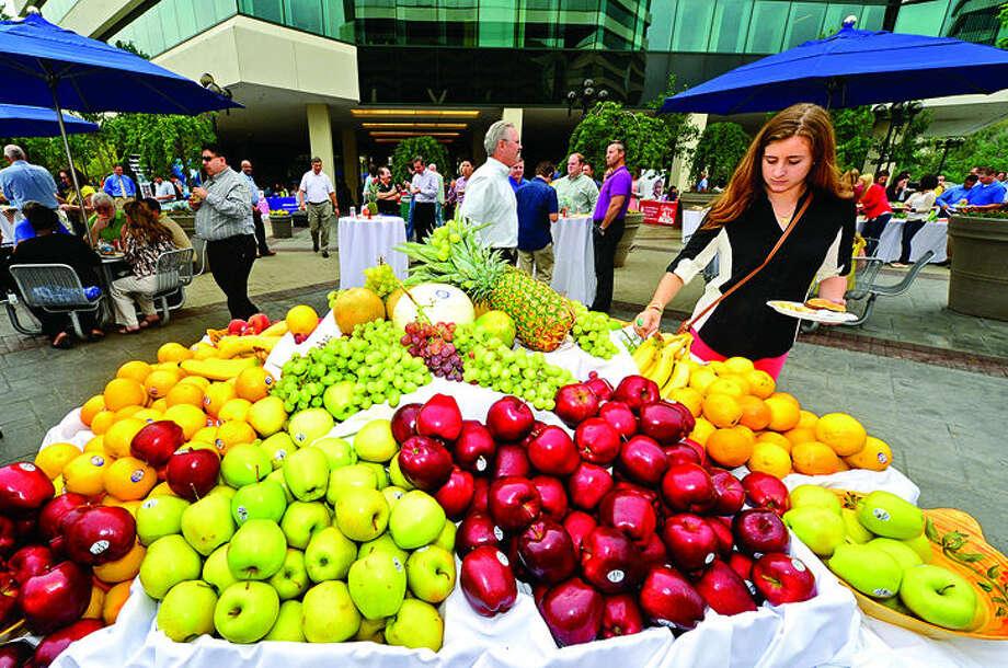 Ipsos employee Erin Fogarty dives into the fresh fruit display during the annual Merritt 7 Tenant Appreciation Picnic Tuesday at 501 and 601 Merritt 7. Hour photo / Erik Trautmann
