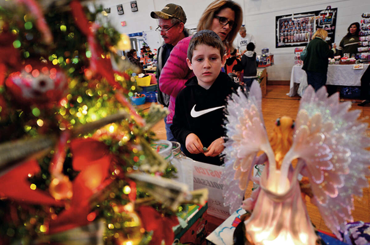 10 year old Tyler Breault chooses raffle items during the St. Ladislaus annual Christmas Fair Saturday. Hour photo / Erik Trautmann