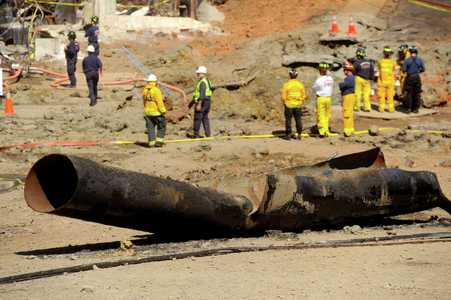 FILE - This Sept. 11, 2010 file photo, a natural gas line lies broken on a San Bruno, Calif., road after a massive explosion. Pacific Gas & Electric Co. expects to pay a total of $565 million in legal settlements and other claims from a deadly 2010 gas pipeline explosion in a San Francisco Bay Area suburb, the utility said. The figure includes $455 million that PG&E has already agreed to pay and $110 million it expects to pay in connection with recent settlements and remaining claims, PG&E said in a filing with federal regulators on Monday, Sept. 9, 2013. (AP Photo/Noah Berger, File) / FR34727 AP