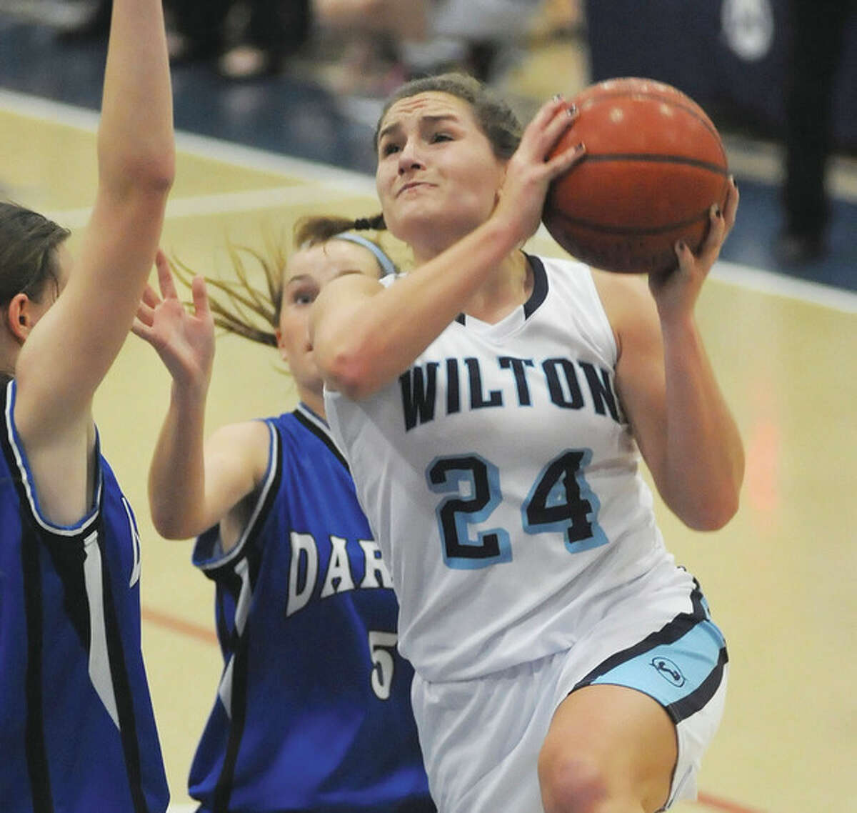 Hour photo/John Nash Wilton's Casey Pearsall, right, goes up for a shot against the defense of Darien's Kate Bushell, right, and Emily Stein, rear, during Wednesday's season-opening game in Wilton.