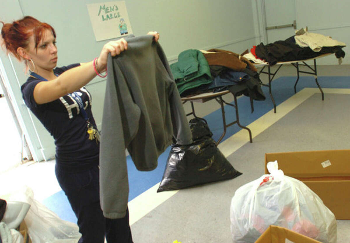 Hour file photo / Erik Trautmann Meghan Masters of Christian Community Action, sorts clothing from the coat drive sponsored by the Norwalk Board of Education and the City of Norwalk which will be given out Saturday at NEON on South Main St.