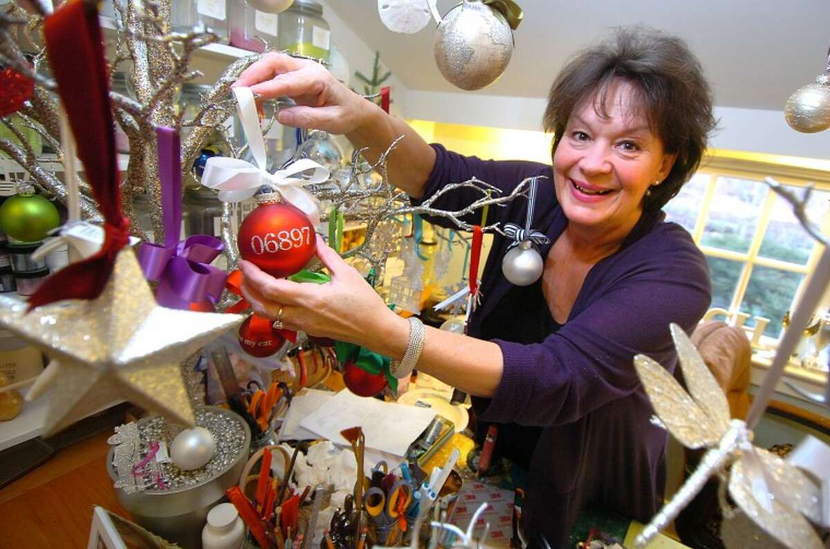 Hour Photo/Alex von Kleydorff. Laurie Davis hangs one of her signature glittered zip code ornaments on a branch in her Glitterworks studio